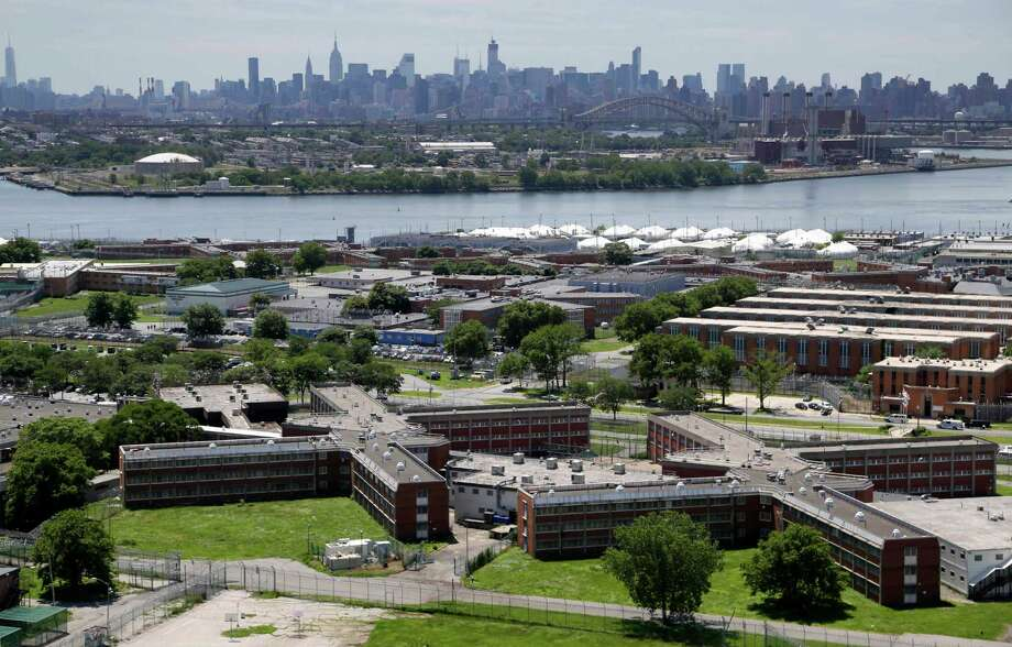 FILE - In this this June 20, 2014, file photo, the sprawling Rikers Island jail complex stands in the foreground with the New York skyline in the climbing into the horizon. A report released Thursday, Jan. 14, 2015 by New York City's Department of Investigation points out problems with the recruiting, hiring and screening of guards who work in the city's jails. The probe found systemic problems with the Department of Correction hiring system, including no recruiting strategy for the past six years, which allowed an alarmingly high number of hires who had arrest records, gang ties or other red flags that are markers for corruption. (AP Photo/Seth Wenig, File) ORG XMIT: NYR403 Photo: Seth Wenig / AP