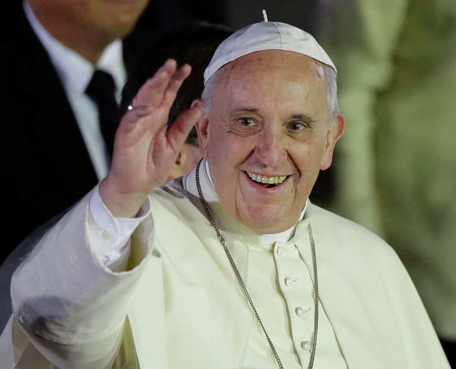 Pope Francis waves to well-wishers upon arrival from Sri Lanka, Thursday, Jan. 15, 2015 at suburban Pasay city, south of Manila, Philippines. Ecstatic crowds greeted the pontiff as he arrived Thursday in the Philippines, Asia's most populous Catholic nation, for the first papal visit in 20 years. (AP Photo/Bullit Marquez) ORG XMIT: XBM102 Photo: Bullit Marquez / AP