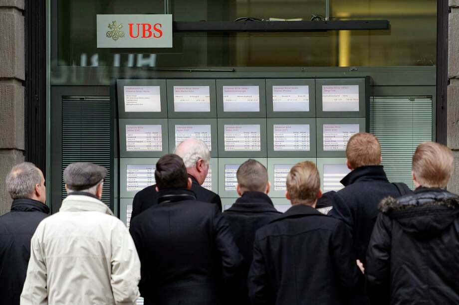 Monitors in Zurich showing stock exchange turbulence drew a crowd after the Swiss National Bank's move. Photo: Walter Bieri, SUB / KEYSTONE