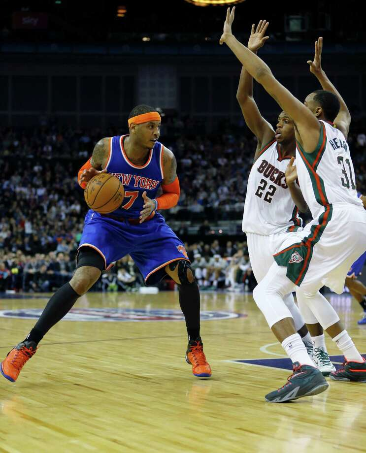 New York Knicks'  Carmelo Anthony, left, competes for the ball with Milwaukee Bucks' Khris Middleton, centre, and John Henson, right, during the NBA basketball game between Milwaukee Bucks and New York Knicks at the O2 Arena in London, Thursday, Jan. 15, 2015. (AP Photo/Kirsty Wigglesworth) ORG XMIT: LKW112 Photo: Kirsty Wigglesworth / AP