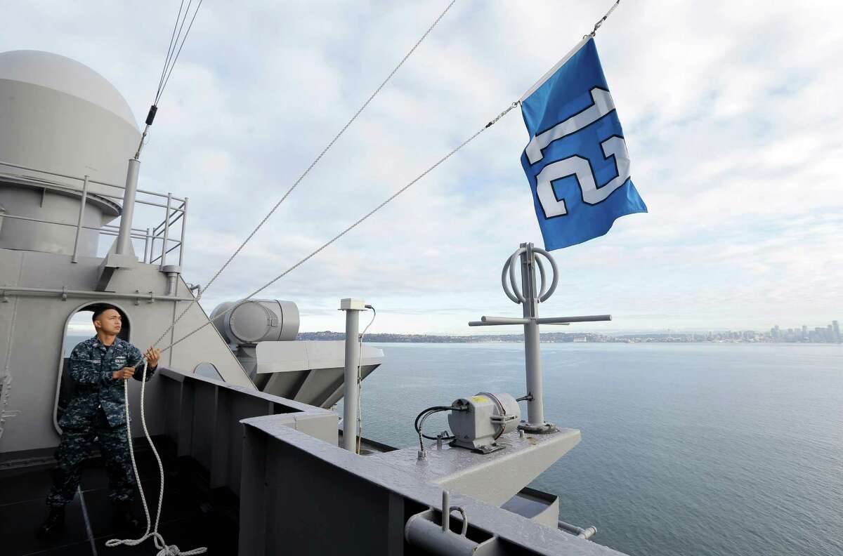 U.S. Navy Quartermaster 1st Class Dave Macaraeg demonstrates how the Seattle Seahawks' 12th Man flag is hoisted up and down while it is flying on the the USS John C. Stennis Navy Aircraft Carrier as the ship moves past Seattle from Naval Base Kitsap in Bremerton to Naval Magazine Indian Island to take on ammunition before a deployment the the Pacific Ocean near San Diego. The Seahawks will play the Green Bay Packers on Sunday, Jan. 18, 2015 in the NFC championship NFL football game.