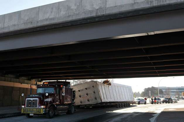 A tractor trailer is seen stopped at the scene of an accident on Fuller Rd. at the Washington Ave. Ext. overpass on Thursday, Jan. 15, 2015, in Albany, N.Y.  A section of a modular home being transported on a trailer, struck the overpass.  (Paul Buckowski / Times Union) Photo: Paul Buckowski
