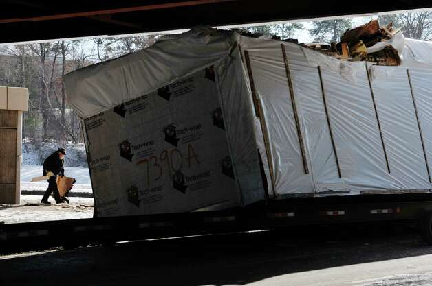 Truck driver Dale Wilburn, owner of Semper Fi Transportation out of Peach Bottom, Pa., collects some of the debris after a section of a modular home being transported by Wilburn, struck a overpass on Thursday, Jan. 15, 2015, in Albany, N.Y.  The accident happened on  on Fuller Rd. at the Washington Ave. Ext. overpass.  (Paul Buckowski / Times Union) Photo: Paul Buckowski
