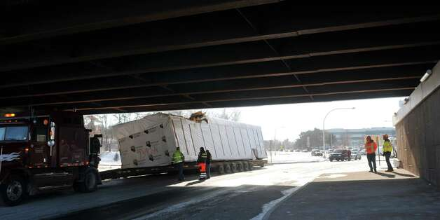 Employees from Roberts Towing and Recovery Specialist out of Glenmont and from New York State DOT work at the scene of an accident on Fuller Rd. at the Washington Ave. Ext. overpass on Thursday, Jan. 15, 2015, in Albany, N.Y.  A section of a modular home being transported on a trailer, struck the overpass.  (Paul Buckowski / Times Union) Photo: Paul Buckowski