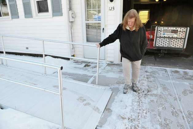 Joanne Sajta uses her foot to show how far out into her driveway the wheelchair ramp went originally on Thursday, Jan. 8, 2015, in Hagaman, N.Y.   The VA had the ramp installed for her husband Peter who needs a wheelchair.  Joanne had to shorten the ramp because they couldn't get their car into the garage the way it was.  (Paul Buckowski / Times Union) Photo: Paul Buckowski / 00030106A