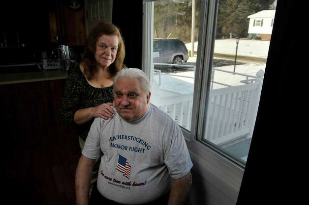 Peter Sajta, foreground, and his wife, Joanne Sajta pose for a photograph inside their home on Thursday, Jan. 8, 2015, in Hagaman, N.Y.  The VA had a wheelchair ramp, seen through the window, installed for Peter who needs a wheelchair.  Joanne and Peter say that the ramp and its construction has problems. (Paul Buckowski / Times Union) Photo: Paul Buckowski / 00030106A
