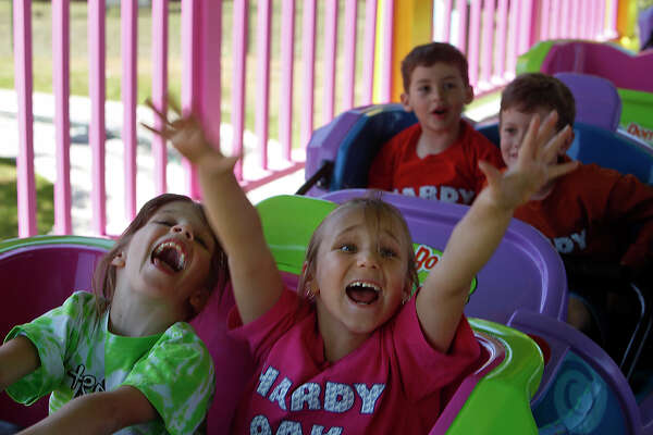 """METRO - Violet Nosker, 6, from left, Alexis Fales, 6, Connor Burrage, 7, and Benjamin Bloom, 6, yell """"YES!"""" when asked by ride operator Jarvis Moore if they want to ride Romp Bomp A Stomp again during the """"Read to Succeed"""" event for first grade students from Hardy Oak Elementary at Six Flags Fiesta Texas on Wednesday, April 8, 2009 in San Antonio. LISA KRANTZ/lkrantz@express-news.net"""
