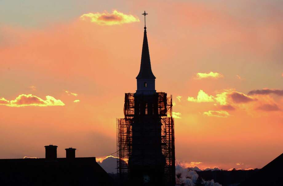 The sun sets behind the scaffold covered steeple of the United Congregational Church on Park Avenue in Bridgeport, Conn. on Wednesday Jan. 7, 2015. Photo: Christian Abraham / Connecticut Post