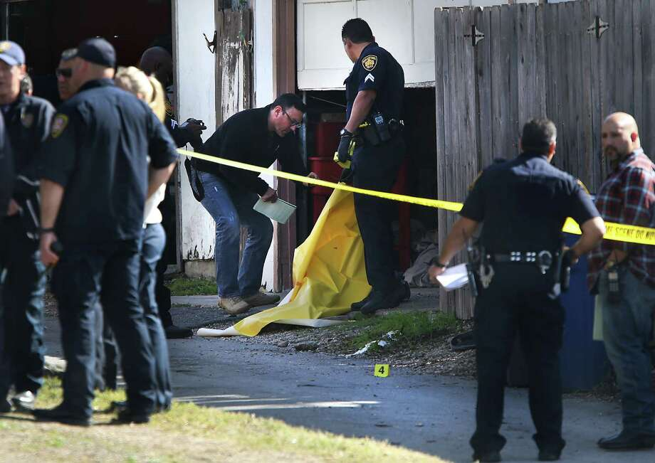 San Antonio Police officers investigate the scene of a double fatality shooting behind the house at 411 Linda Drive.   Friday, Jan. 16, 2015. Photo: BOB OWEN, San Antonio Express-News / © 2014 San Antonio Express-News