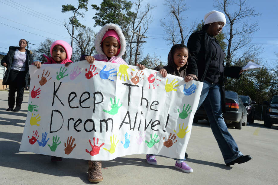 From left Kennendy Kirkwood, Kaidence Charles and Aleecya Johnson hold a banner during Lucas Elementary's Martin Luther King parade on Friday. Students were let out of class to follow the Central High School band around the campus. Another parade will start Saturday at 10:00 a.m. at Beaumont's Lamar Institute of Technology and travel along Lavaca Street, Highland Avenue and Irving Avenue. April Prejean, right, is also pictured.