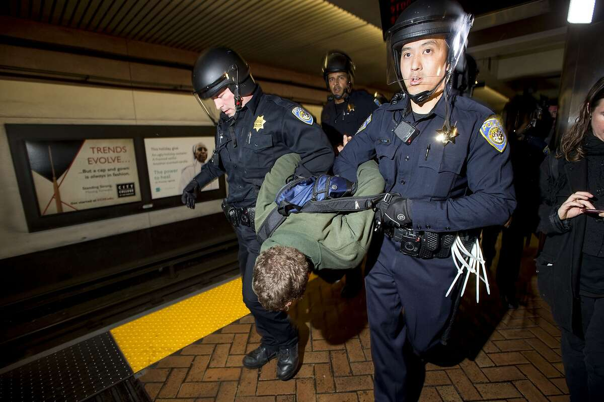 Police officers arrest a protester who banged a spoon on a subway car during a demonstration at the Bay Area Rapid Transit Montgomery station on Friday, Jan. 16, 2015, in San Francisco. About 80 demonstrators rallied in support of 14 anti-police violence protesters arrested in November for blocking trains at an Oakland BART station. (AP Photo/Noah Berger)