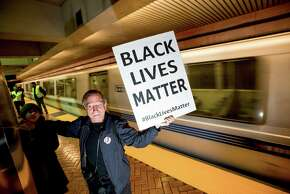 George Cammarota protests against police violence at the Bay Area Rapid Transit Montgomery station on Friday, Jan. 16, 2015, in San Francisco. About 80 demonstrators disrupted train service while rallying in support of 14 anti-police violence protesters arrested in November for blocking trains at an Oakland BART station. (AP Photo/Noah Berger)
