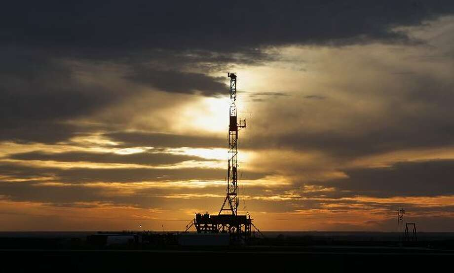 This Feb. 17, 2014 photo shows a drilling rig in Howard County, Texas as the sun sets. (AP Photo/Houston Chronicle, James Nielsen)