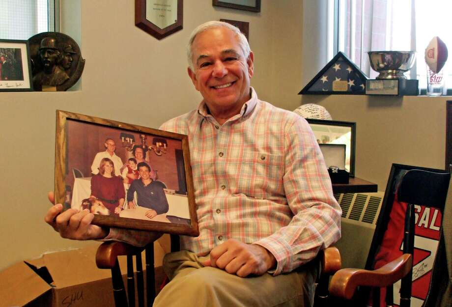 Stamford native Bobby Valentine will mark two years as Sacred Heart University's athletic director next month. Valentine, shown here in his office, credits his parents, Joe and Grace, for his work ethic. They are shown in the photo he's holding from 1986. Valentine and his wife, Mary, are seated. The baby is Bobby Valentine Jr. Photo: Brian Koonz / Connecticut Post