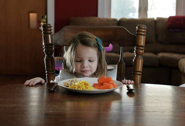 Photo illustration of Zoey Stebbins, 2, with a  plate of chicken and corn and carrots at her home on Tuesday, Jan. 13, 2015, in Cohoes, N.Y.  (Paul Buckowski / Times Union) Photo: Paul Buckowski / 00030136A