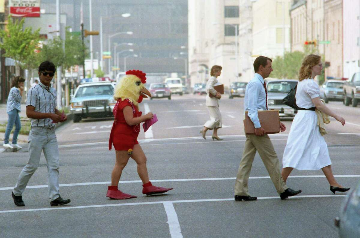 See the interesting interesting lengths that Houston businesses have gone to attract customers... Lynn Jasso, dressed as a chicken to advertise a downtown barbecue restaurant, mingles with pedestrian traffic as she crosses San Jacinto at Preston in May 1987.