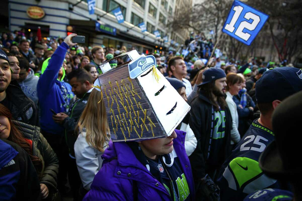 Leslie Listy wears a homemade cheese grater during a Seahawks rally at Westlake Park in advance of Sunday's NFC championship game against Green Bay. Hundreds of fans showed up to cheer for their team in advance of the big game.
