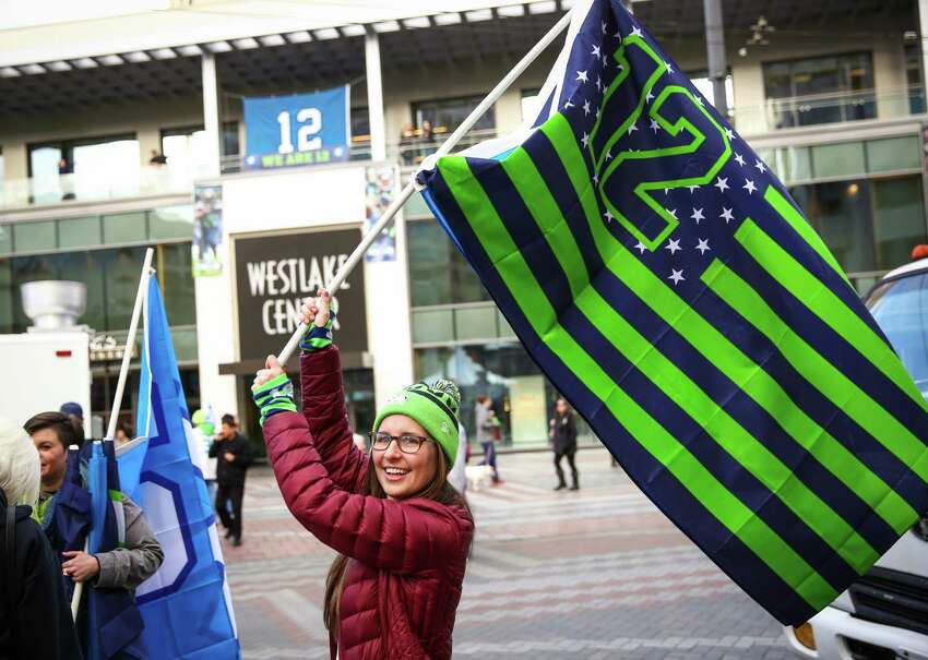 Erin Staadecker waves a flag during a Seahawks rally at Westlake Park in advance of Sunday's NFC championship game against Green Bay. Hundreds of fans showed up to cheer for their team in advance of the big game.