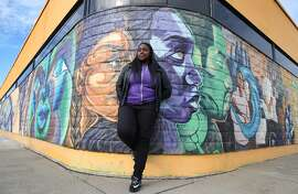 Gemikia Henderson is seen with murals created by visual arts students at the RYSE youth center in Richmond, Calif. on Friday, Jan 9, 2015. Henderson has worked on a number of video documentaries for the center. The student members of the center are using their artistic talent as a way to respond to social issues affecting their lives.