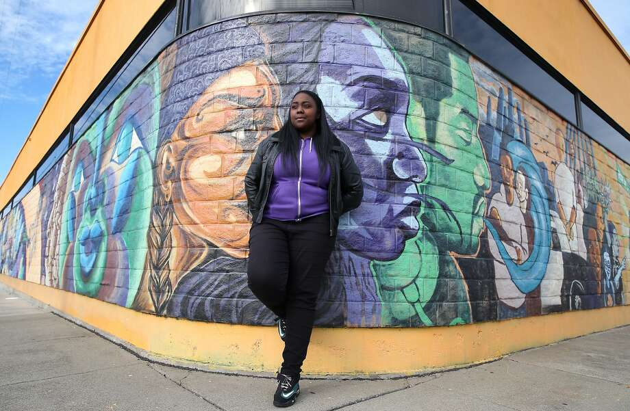 Gemikia Henderson is seen with murals created by visual arts students at the RYSE youth center in Richmond, Calif. on Friday, Jan 9, 2015. Henderson has worked on a number of video documentaries for the center. The student members of the center are using their artistic talent as a way to respond to social issues affecting their lives. Photo: Paul Chinn, The Chronicle