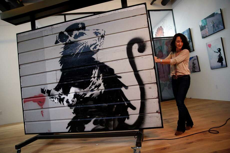 """Agnes Faure moves """"Haight Street Rat"""" at 836M. Created in the Haight, the graffiti art is now on view on Montgomery Street. Photo: Scott Strazzante / The Chronicle / ONLINE_YES"""