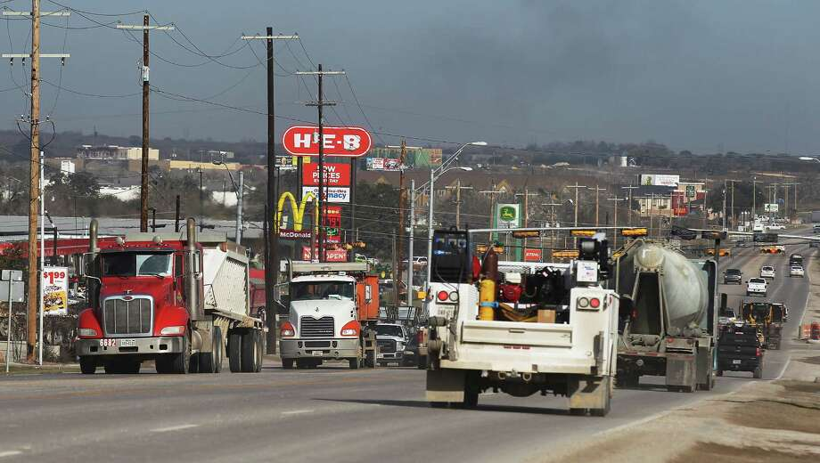 Work trucks make their way along a busy U.S. 181 in Kenedy on Friday. Recent drops in oil prices have resulted in job cuts in the industry. Despite the price slump, local officials have not seen any slowdown in the town located in the heart of Eagle Ford. (Kin Man Hui/San Antonio Express-News) Photo: Kin Man Hui /San Antonio Express-News / ©2015 San Antonio Express-News