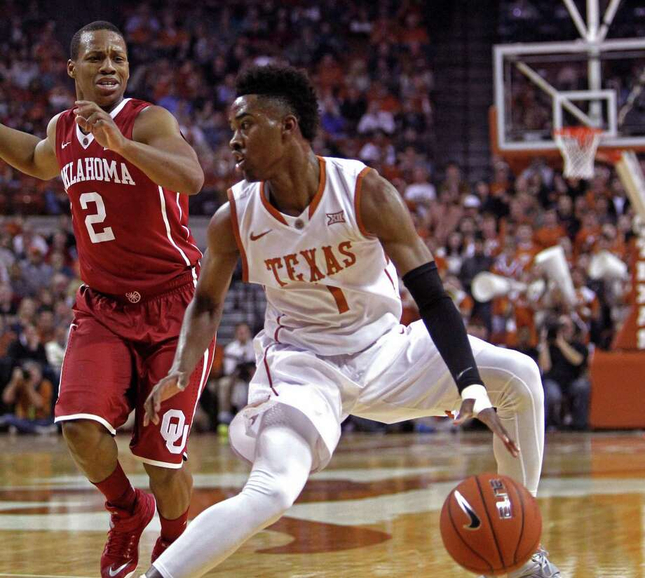 Texas guard Isaiah Taylor (1) looks to drive against Oklahoma guard Dinjiyl Walker (2) during the first half an NCAA college basketball game, Monday, Jan. 5, 2015, in Austin. Photo: Michael Thomas /Associated Press / FR65778 AP
