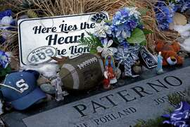 Items are left at the grave of Joe Paterno, the late head football coach of Penn State, on Friday in State College, Pa.. The NCAA restored 112 of Paterno's 409 career wins, again making him the winningest coach in major college football history.