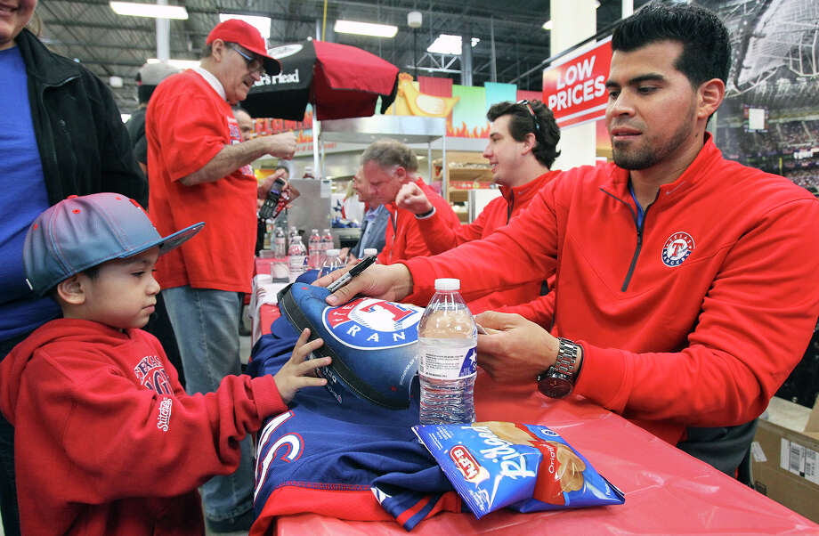 Catcher Robinson Chirinos signs a jersey for young fan Aristeo Jimenez as Ranger's baseball players sign autographs at the HEB in Universal City during a stop in their Rangers' Winter Caravan on January 16, 2015. Photo: Tom Reel / San Antonio Express-News