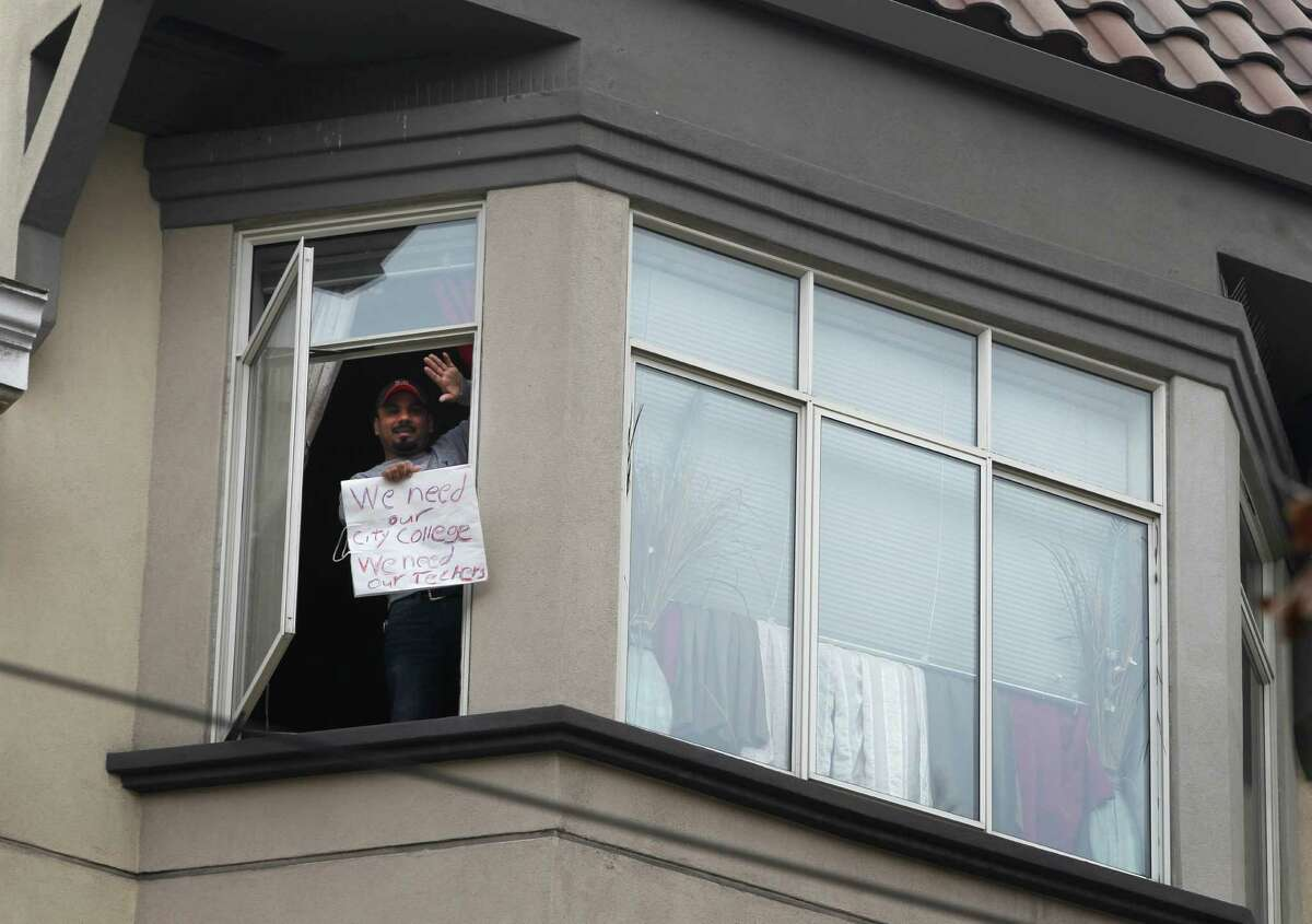 A neighbor who lives across the street from the CCSF Civic Center campus waves to faculty and students that gathered before their march to the steps of City Hall in San Francisco, Calif. on Friday, Jan. 16, 2015. The faculty and students are angered by the state-appointed special trustee's decision to close the Eddy Street building.