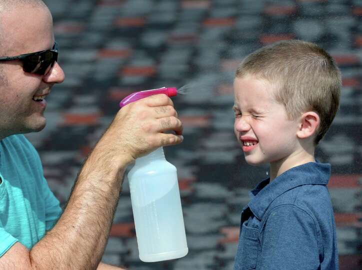 John Gloss uses a spray bottle to cool off his son, John Ricard Gloss, 4, of Frederick, Md., as they