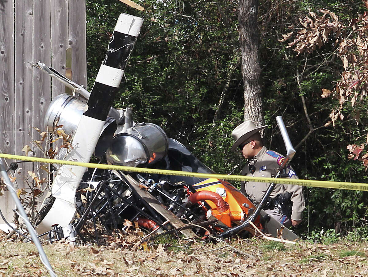 A Texas State trooper on Friday investigates the scene of a helicopter crash in a field near Texas 242 and Gosling in The Woodlands. The pilot, Michael Gene Mims, 51, of Conroe, a Montgomery County businessman and deacon at St. Anthony of Padua Catholic Church in The Woodlands, was pronounced dead at the scene. Story on page B3.