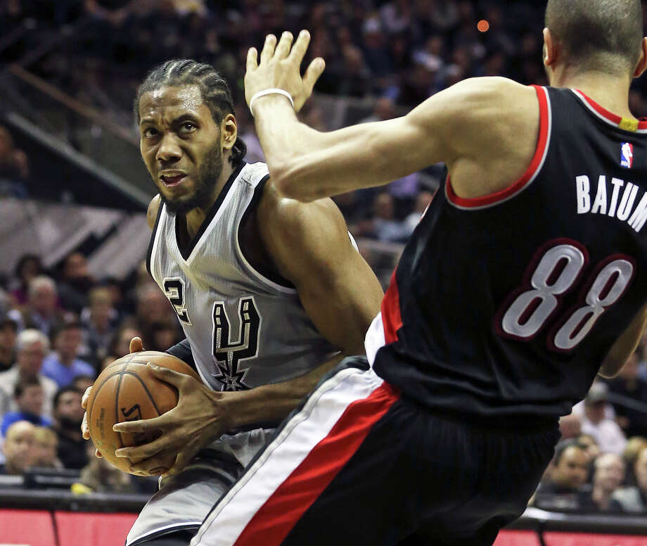 Kawhi Leonard shoves into the lane against Nicolas Batum as the Spurs play the Portland Trailblazers at the AT&T Center on January 16, 2015. Photo: Tom Reel / San Antonio Express-News