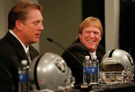 Oakland Raiders owner Mark Davis, right, smiles as he listens to the Raiders' new head coach Jack Del Rio, left, answer a question from a member of the media during a press conference introducing Del Rio at the team headquarters Jan. 16, 2015 in Alameda, Calif.