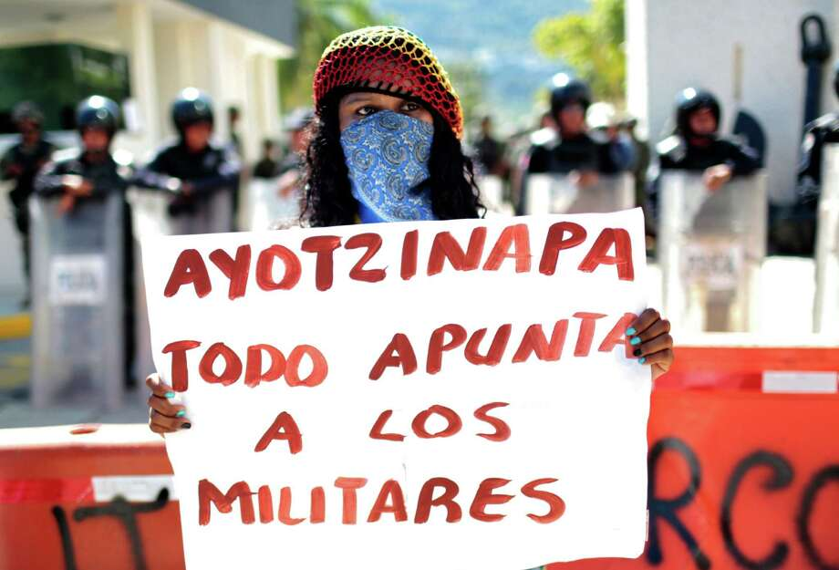 """A woman holds a banner reading """"Ayotzinapa, everything points to the military"""" during a protest demanding justice. Photo: Pedro Pardo /Getty Images / AFP"""