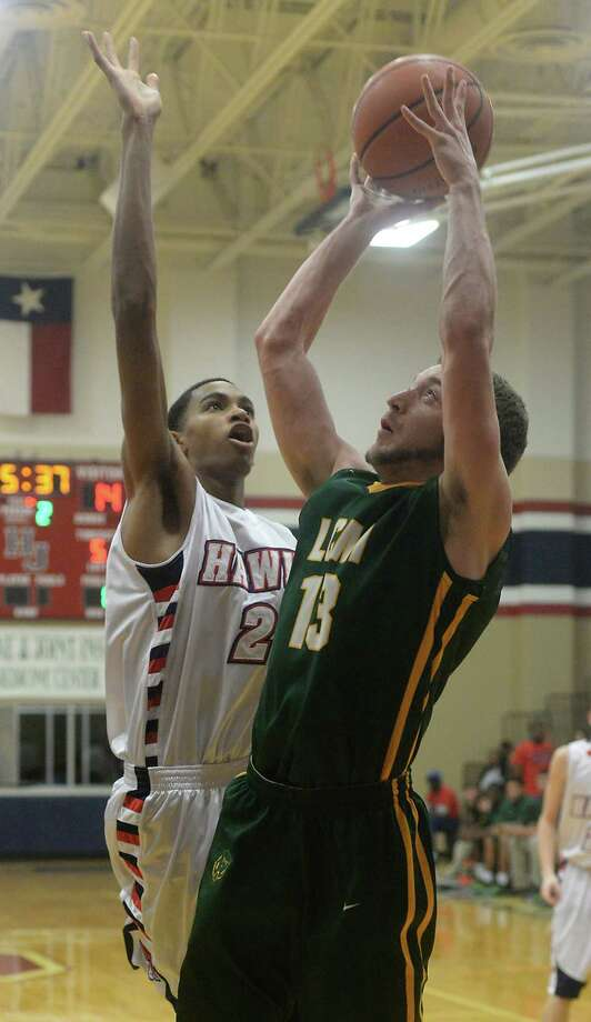 Hardin-Jefferson's Jamerson Roberts defends as Little Cypress-Mauriceville's Andrew Daspit puts up his shot during Friday's match-up at Hardin-Jefferson.  Photo taken Friday, January 16, 2015  Kim Brent/The Enterprise Photo: KIM BRENT / Beaumont Enterprise