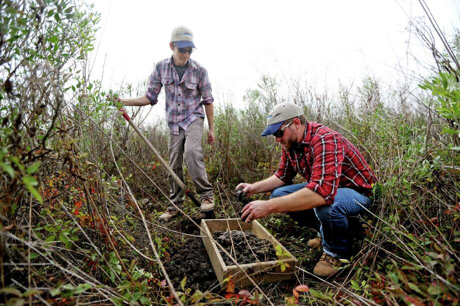 David Treichel, left, field director, and Charles Bludau, senior project manager for HRA Gray & Pape, pick through clay looking for artifacts while conducting an archaeological site survey for a development planned in Brazoria County. Photo: Gary Coronado, Staff / © 2014 Houston Chronicle