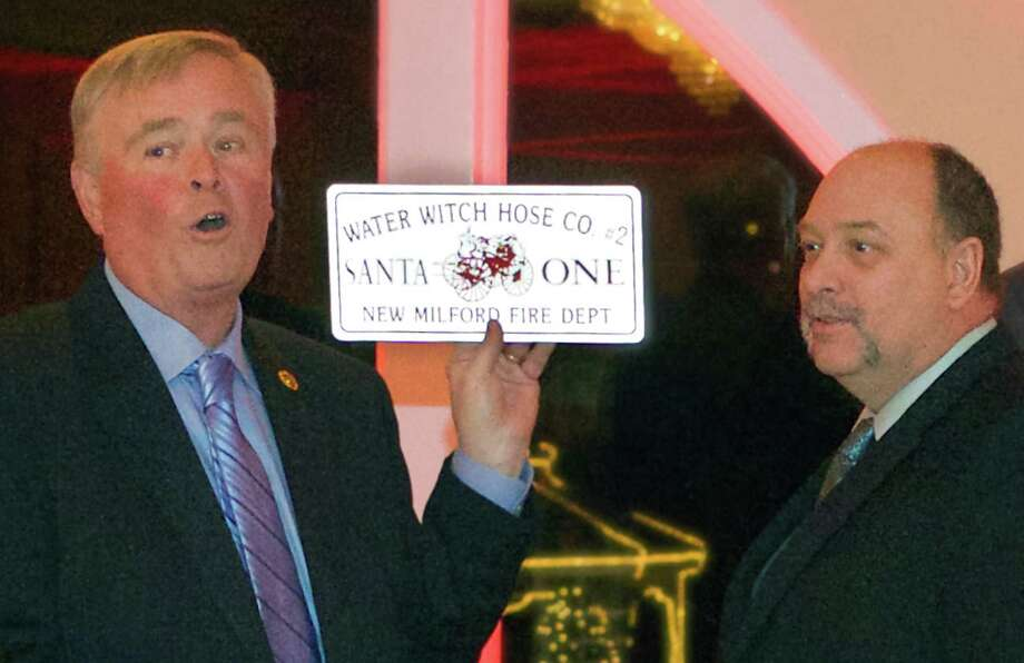 David Lathrop, left, displays a 'Santa One' license plate as he helps honor fellow firefighter Ron Peet, who's been known to bond with Santa Claus each holiday season. Peet was among those to take their bows during Water Witch Hose Co. No. 2's annual dinner-dance at the Candlewood Inn in Brookfield. Jan. 9, 2015 Photo: Trish Haldin / The News-Times Freelance