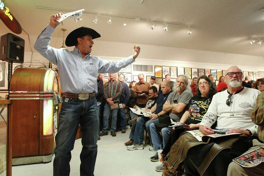 Dennis Cisneros (left) reaches out to buyers placing bids on an item as Burley Auction Gallery holds a sale for Eddie Wilson, Founder of Armadillo World Headquarters and Threadgill's Restaurants, in New Braunfels on Saturday, Jan. 17, 2015. Wilson's collection of Texas memorabilia, concert posters, Janis Joplin items and other Texas-based items went on sale to the highest bidders in a packed house of several hundred potential buyers. Over 500 items were on sale at the auction. Photo: Kin Man Hui, San Antonio Express-News / ©2015 San Antonio Express-News