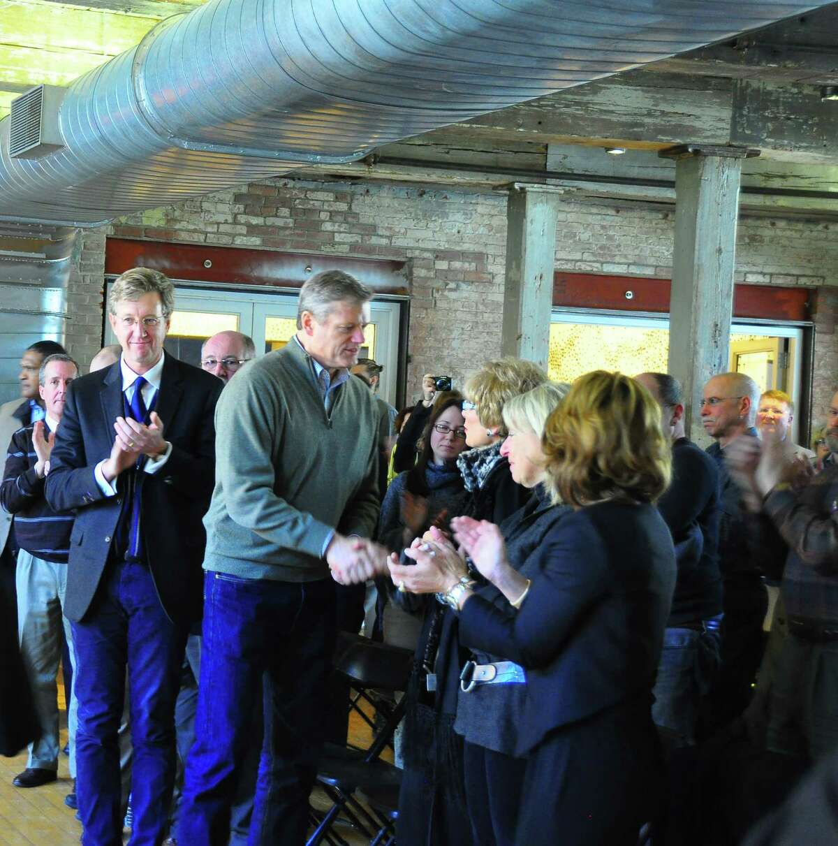 New Masscachusett Gov. Charlie Baker, center, greets visitors at Mass MoCA on Saturday, Jan. 10, 2015, during part of Baker's Spotlight on Excellence tour. The museum's Phase III expansion, due to be completed for an opening in early 2017, will almost double to exhibition space, to 260,000 square feet. The project is being paid for by $30 million in private funding raised by the museum and a $25.4 million state grant announced in August. The museum's director, Joseph Thompson, is behind baker. (Photo by Jason Kraus/Special to the Times Union)