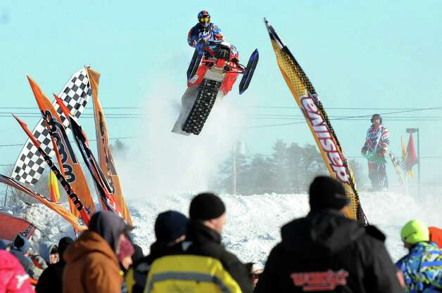 A snowmobiler takes a jump during East Coast Snocross on Saturday, Jan. 17, 2015, at Schaghticoke Fair Grounds in Schaghticoke, N.Y. The event continues Sunday with gates opening at 9 a.m. and finals concluding by 3:30 p.m. Admission is $15 for adults. Children age 7 and under are free with a paying adult. (Cindy Schultz / Times Union) Photo: Cindy Schultz / 00030250A
