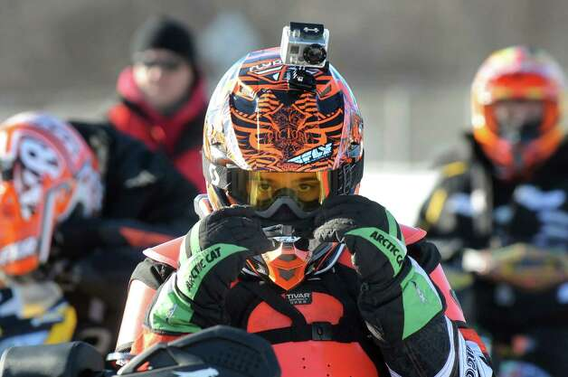 Travis Emery, 13, of Spofford, N.H., center, adjusts his helmet, complete with a GoPro camera, as he waits to compete in junior classes during East Coast Snocross on Saturday, Jan. 17, 2015, at Schaghticoke Fair Grounds in Schaghticoke, N.Y. The event continues Sunday with gates opening at 9 a.m. and finals concluding by 3:30 p.m. Admission is $15 for adults. Children age 7 and under are free with a paying adult. (Cindy Schultz / Times Union) Photo: Cindy Schultz / 00030250A