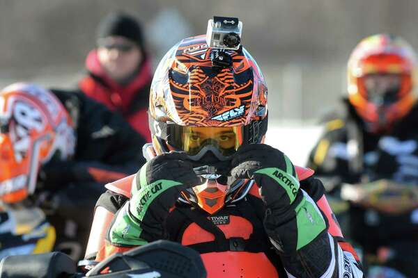 Travis Emery, 13, of Spofford, N.H., center, adjusts his helmet, complete with a GoPro camera, as he waits to compete in junior classes during East Coast Snocross on Saturday, Jan. 17, 2015, at Schaghticoke Fair Grounds in Schaghticoke, N.Y. The event continues Sunday with gates opening at 9 a.m. and finals concluding by 3:30 p.m. Admission is $15 for adults. Children age 7 and under are free with a paying adult. (Cindy Schultz / Times Union)