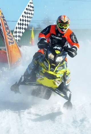 A snowmobiler carves his sled through the snow during East Coast Snocross on Saturday, Jan. 17, 2015, at Schaghticoke Fair Grounds in Schaghticoke, N.Y. The event continues Sunday with gates opening at 9 a.m. and finals concluding by 3:30 p.m. Admission is $15 for adults. Children age 7 and under are free with a paying adult. (Cindy Schultz / Times Union) Photo: Cindy Schultz / 00030250A
