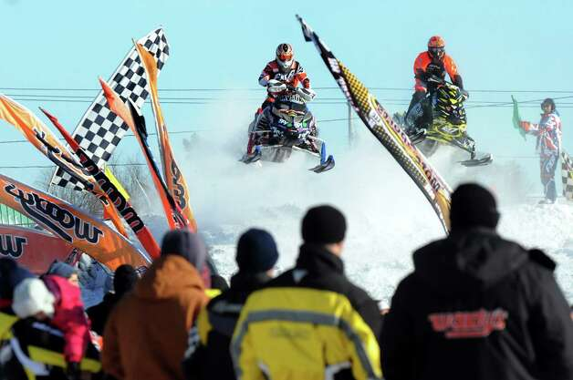 Snowmobilers takes a jump during East Coast Snocross on Saturday, Jan. 17, 2015, at Schaghticoke Fair Grounds in Schaghticoke, N.Y. The event continues Sunday with gates opening at 9 a.m. and finals concluding by 3:30 p.m. Admission is $15 for adults. Children age 7 and under are free with a paying adult. (Cindy Schultz / Times Union) Photo: Cindy Schultz / 00030250A