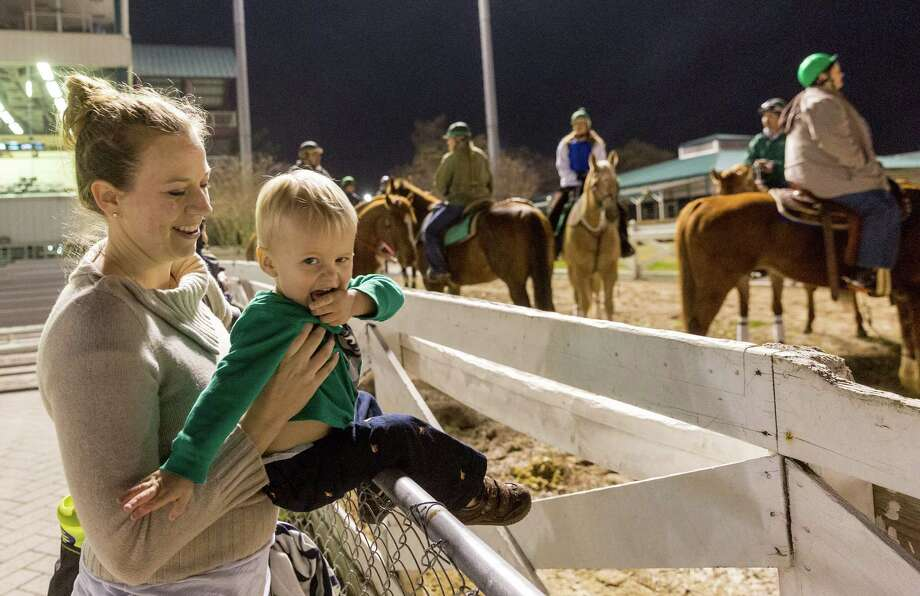 Action/scene from the opening night of racing at Sam Houston Race Park. Sam Houston Race Park, 7575 N. Sam Houston Parkway West. ID: Mom Alison Irvine of Cypress, Texas holds Andrew Irvine, age 2, so he can get a good look at the horses. Friday January 16, 2015 Photo: Craig Hartley, For The Chronicle / Copyright: Craig H. Hartley