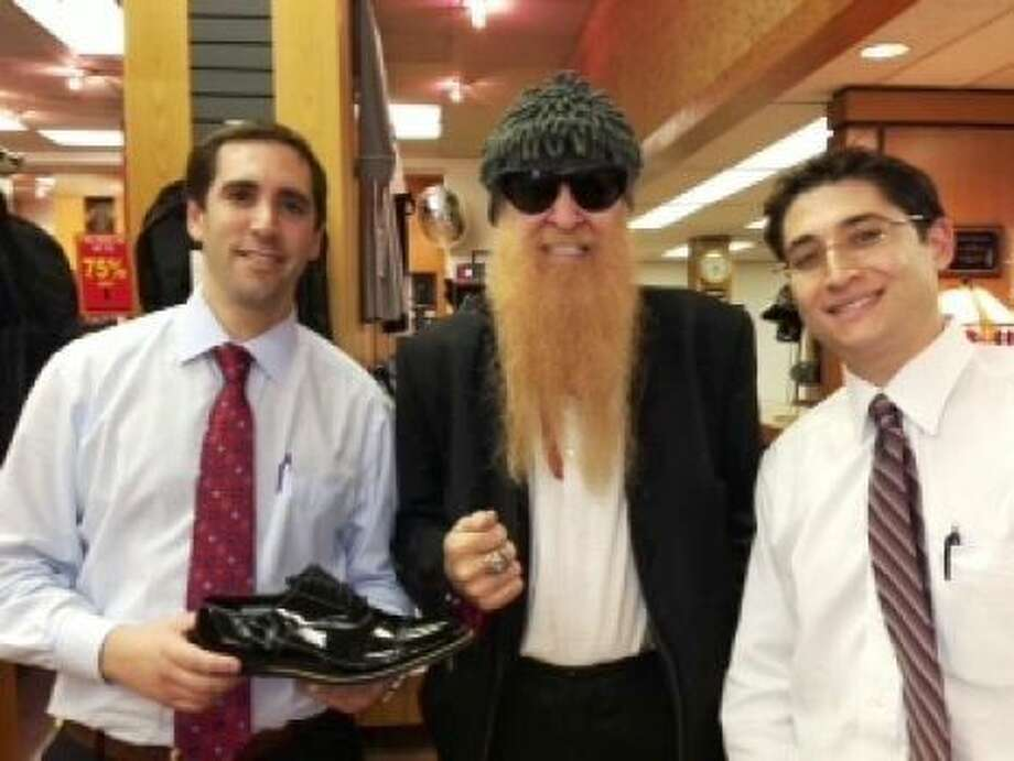 On a different tour, Billy Gibbons of ZZ Top stopped by Penner's to do some shopping. He's flanked by Matt Penner (holding shoe) and Mitchell Penner (right). Photo: Courtesy Penner's