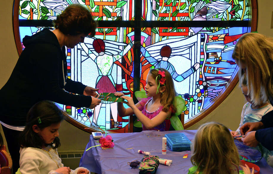 Joan Pihonak, of Stratford, helps her daughter Riley, 8, create her fairy costume, during Fairy Magic Party held at the Stratford Library in Stratford, Conn. on Saturday Jan. 17, 2015. Rainbow Magic Fairies is a popular children's book series by author Daisy Meadows. At the party, children are encouraged to dress up as one of their favorite fairies. Games and other fun activities were also held for them. Photo: Christian Abraham / Connecticut Post