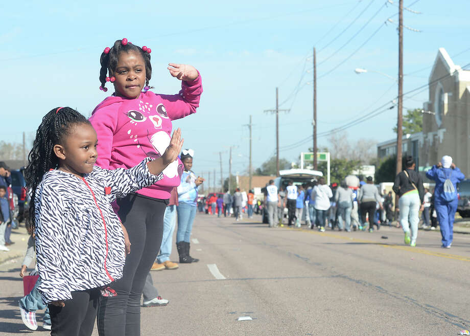 Mylae Mitchell (left) and Tierah Moore wave as the parade passes during the Martin Luther King, Jr., birthday parade through Beaumont Saturday morning. Schools, businesses, politicians and other community groups joined in the event, throwing out candy to the families lining the streets. 