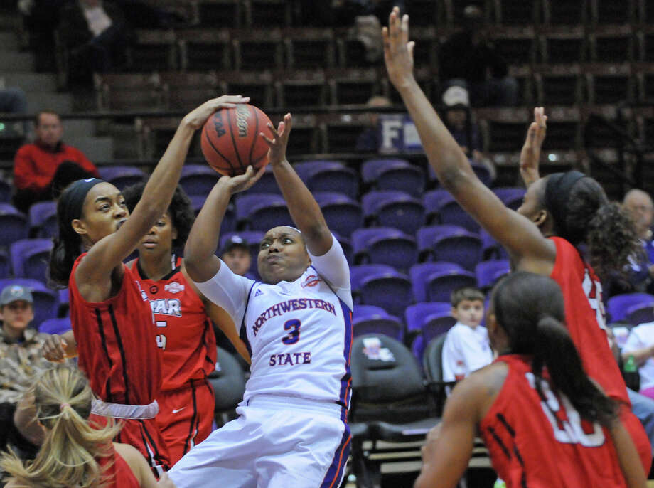 Lamar's Caroline Adesulu (15) blocks the shot of Northwestern State's Keisha Lee (3) during Saturday's game. The Lady Cardinals won 82-72. Photo courtesy of NSU Photo Lab